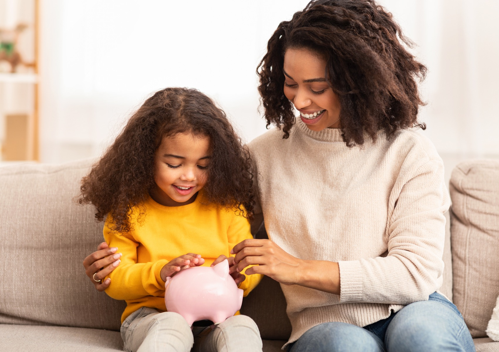 cheerful-mother-teaching-daughter-how-to-save-money-at-home-picture-id1201448916
